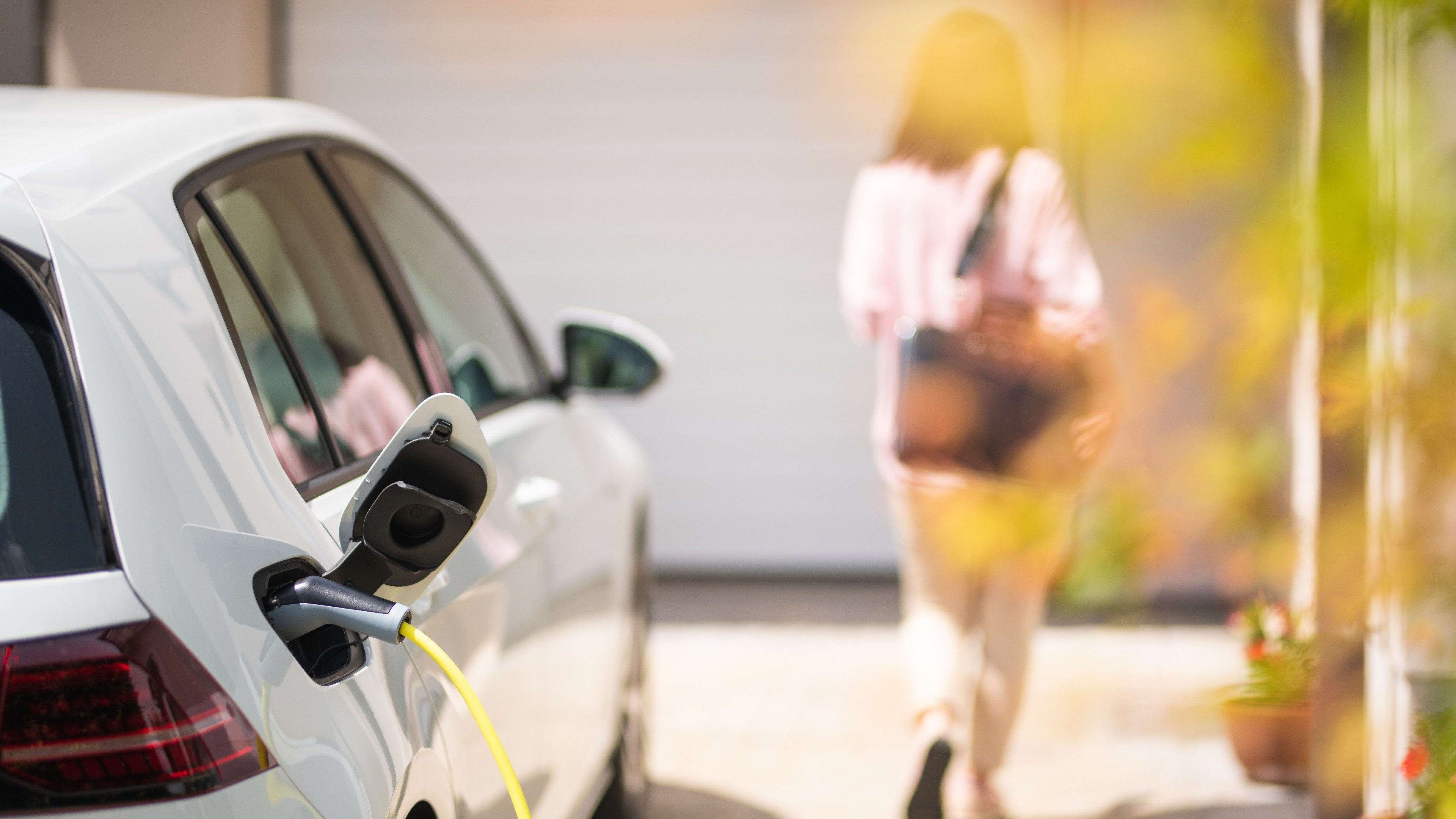 Close up of a electric car charger with female silhouette in the background